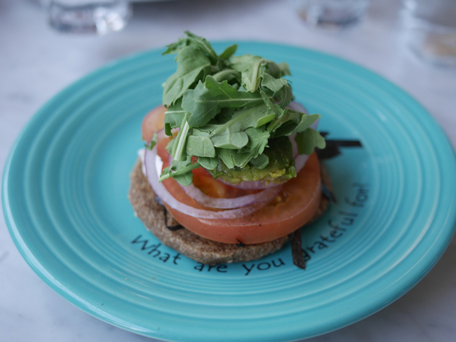 Peace - Raw open-faced bagel with onion-sesame crust, cashew cream cheese, nori, tomato, onion, capers and sprouts.