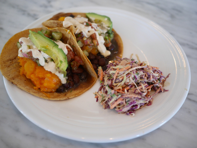Two organic tacos with chipotle butternut squash, black beans, avocado, seasonal salsa fresca, and cashew nacho cheese. Served with a side of Mexican coleslaw